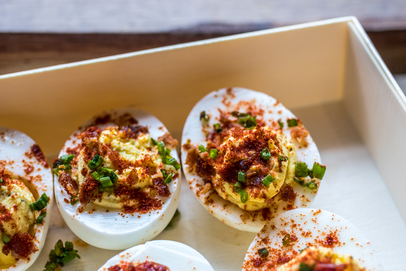 Deviled Eggs: locally sourced eggs cut in half and filled with whipped mustard, mayo, dill, and cayenne then topped with bacon and chive / Image: Catherine Viox{ }// Published: 7.16.20