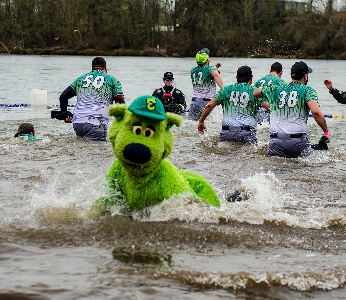 The Eugene Emerald baseball team taking the plunge.� Plungers and onlookers gather for the annual Special Olympics Polar Plunge at Maurie Jacobs Park in Eugene. With over 250 plungers diving into the Willamette River, participants look to surpass $412,000, which was last years total. Eugene is just one of the five locations around Oregon that hosts the plunge, but is a nationwide event. The funds raised by todayâ��s plunge will go towards assisting Oregon Special Olympic teams. Photo by Kara Jenness, Oregon News Lab.