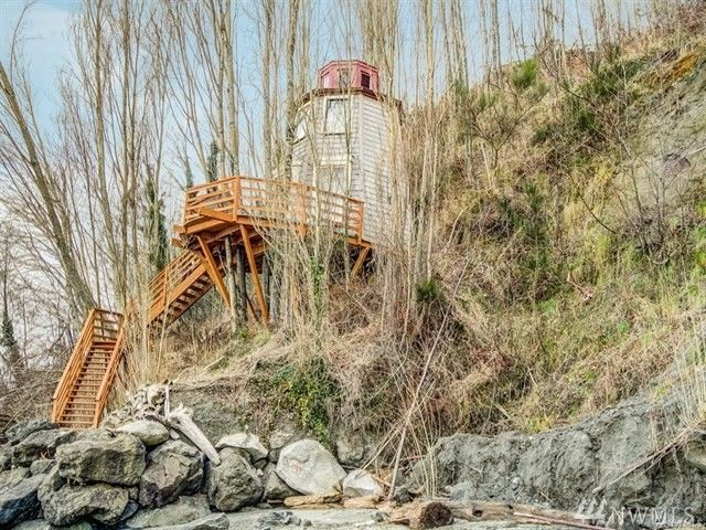 You can't say the word 'treehouse' in this market without thinking of Pete Nelson, the genius behind Animal Planet's hit show, 'Treehouse Masters'. This Magnolia treehouse - shaped more like a lighthouse - is one of Nelson's, and you've likely seen it along the bluff since it's build in 2014. You may also remember some hubbub last year, when the city sued the current property owner for the structure not being up to code. In fact, it was looking like the little guy may be torn down. BUT those issues must have been resolved, as low-and-behold - the little house that could is back on the market, selling by Windermere's Dave Reith for $139,000. More info online at windermere.com, MLS #{ }1263411. (Image: Windermere){ }