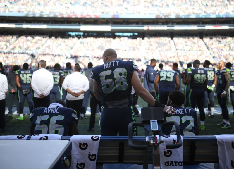 The Seattle Seahawks' Cliff Avril joins Michael Bennett on the bench during the national anthem before tonight's game against the The Kansas City Chiefs. Teammate Justin Britt stands next to Bennett with hand on his shoulder. (Photo: KOMO News/KOMO Sports)