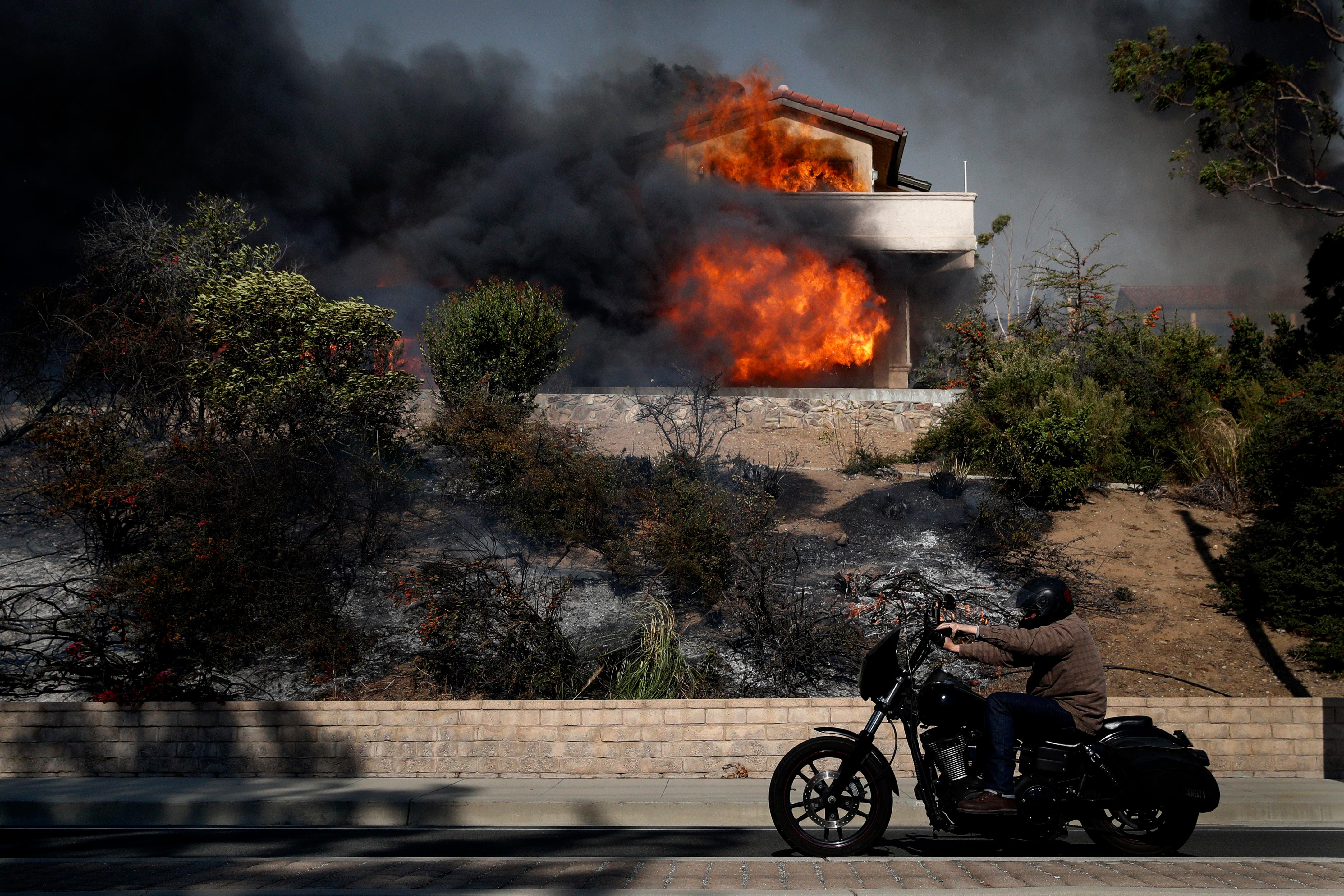 A man rides his bike past a home consumed by a wildfire Tuesday, Dec. 5, 2017, in Ventura, Calif. (AP Photo/Jae C. Hong)