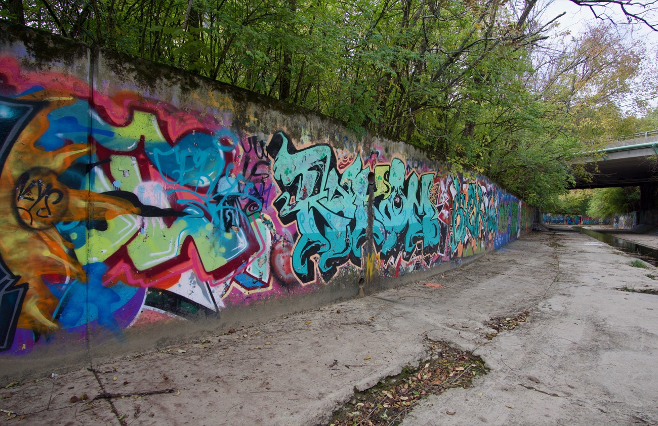 The decorated walls along Duck Creek have been claimed by graffiti artists whose works sit cramped atop each other like the layers of a spray-paint palimpsest. Duck Creek, as it existed a century ago, will never exist again. But the works of graffiti left in its trace will continue to simulate the spellbinding mania of a creek bed in full bloom. / Image: Brian Planalp // Published: 11.5.18