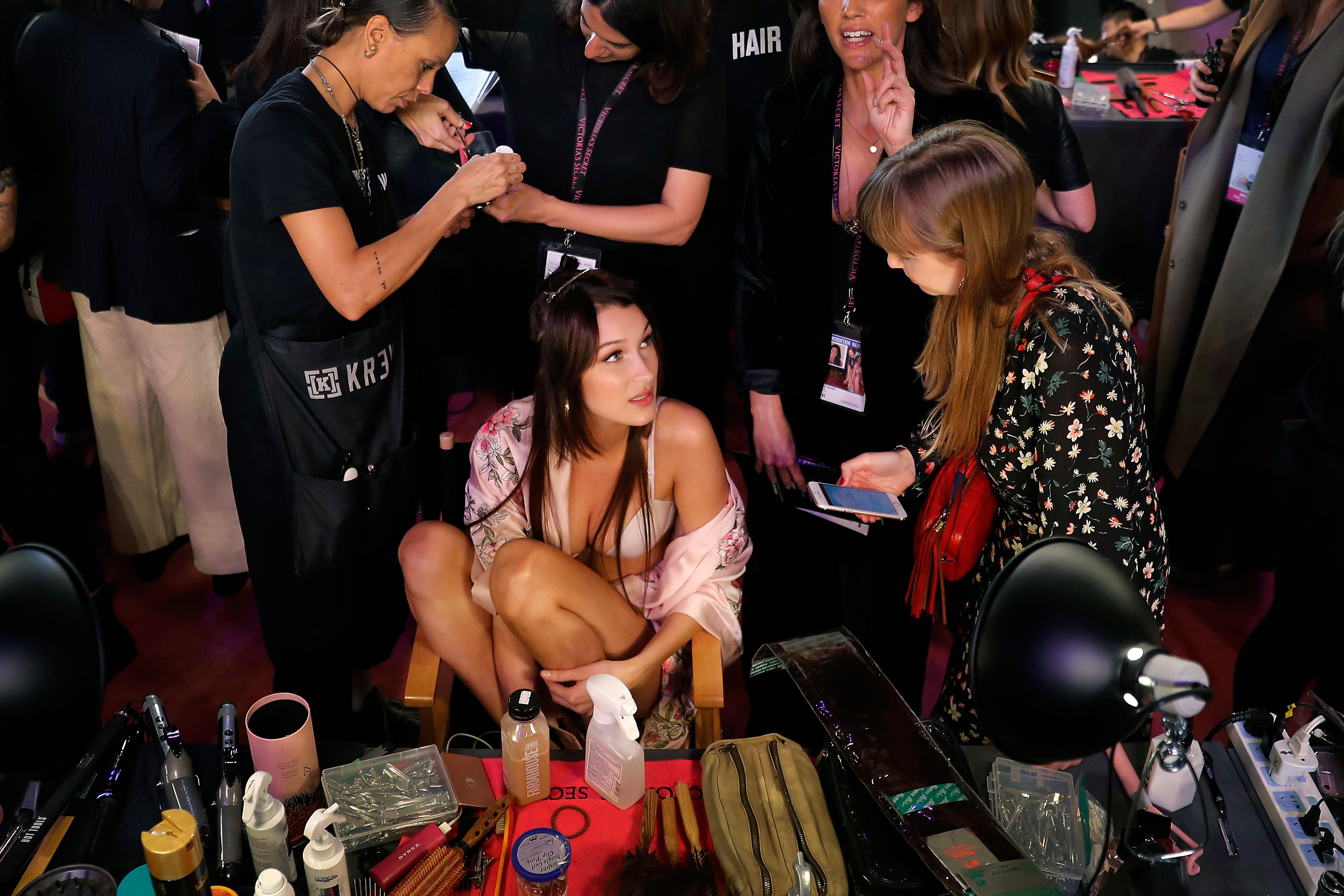 Model Bella Hadid of the United States talks to a woman as she is made up at backstage before the Victoria's Secret fashion show inside the Mercedes-Benz Arena in Shanghai, China, Monday, Nov. 20, 2017. The Victoria's Secret fashion show takes place in Shanghai on Monday with performances from Singer Harry Styles and R&B star Miguel. (AP Photo/Andy Wong)
