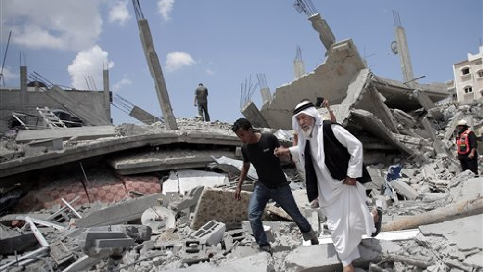 An elderly Palestinian man makes his way on the rubble of a destroyed house following Israeli strikes in Rafah refugee camp, southern Gaza Strip, Monday, Aug. 4, 2014. (AP Photo/Khalil Hamra)