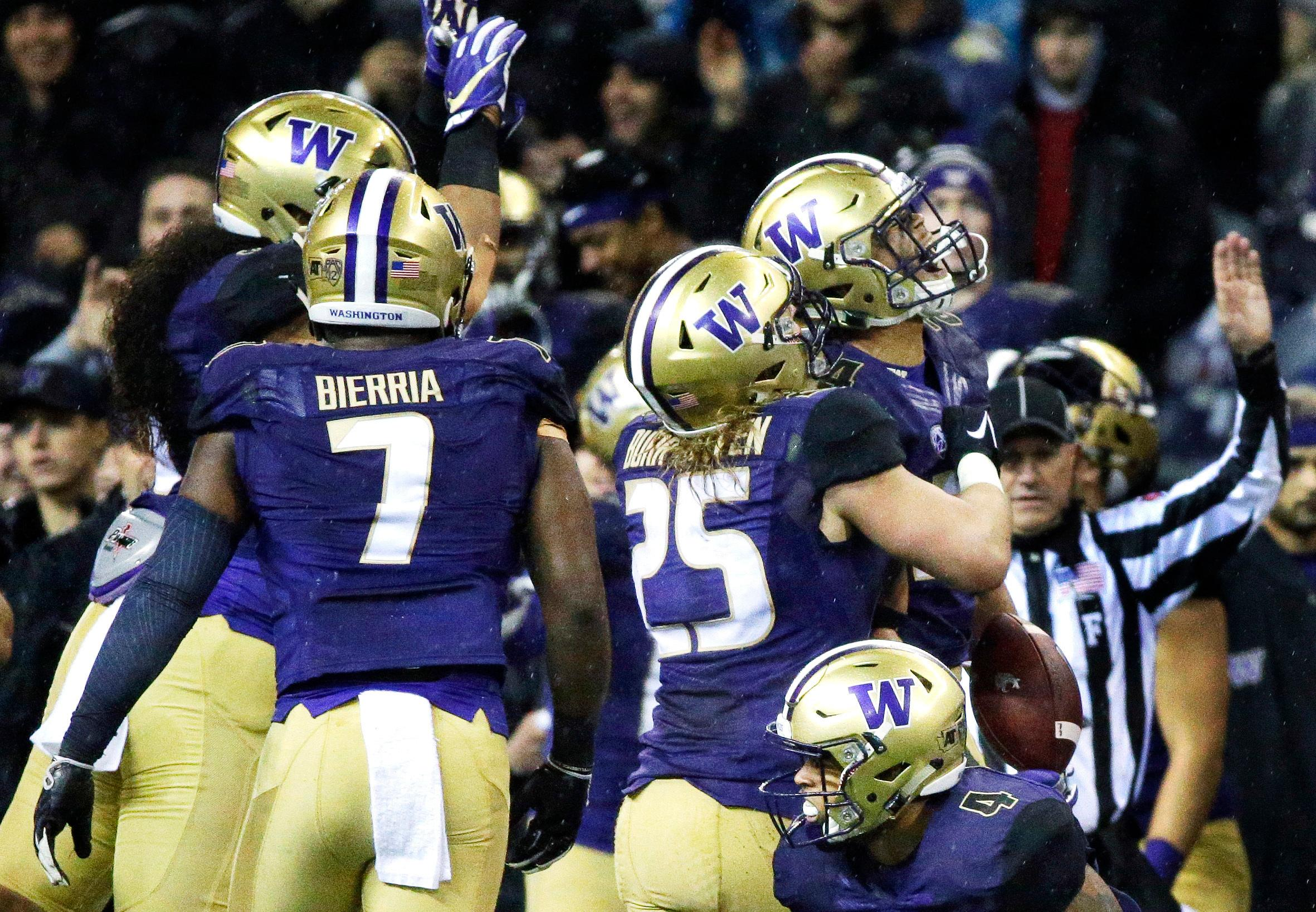 Washington defensive back Ezekiel Turner, upper right, celebrates with linebacker Ben Burr-Kirven (25) after Turner intercepted a pass during the first half of an NCAA college football game against Washington State, Saturday, Nov. 25, 2017, in Seattle. (AP Photo/Ted S. Warren)