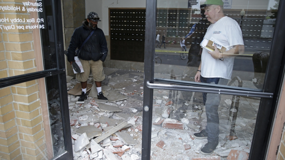 Jorge Sanchez, left, and Rob Doughty, right, look over damage to the main post office following an earthquake Sunday, Aug. 24, 2014, in Napa, Calif. A large earthquake caused significant damage in California's northern Bay Area early Sunday, sending at least 70 people to a hospital, igniting fires, knocking out power to tens of thousands and sending residents running out of their homes in the darkness. (AP Photo/Eric Risberg)
