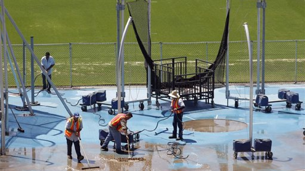 Workers remove water from the shot put area at Drake Stadium at UCLA, Wednaesday, July 30, 2014, after a burst 93-year-old pipe left the Los Angeles campus awash in millions of gallons of water in the middle of California's worst drought in decades. The water also flooded the school's storied basketball court less than two years after a major renovation. (AP Photo/Nick Ut)