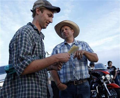 Ammon Bundy, right, talks with Spencer Shillig at the Lake Mead National Recreation Area near Overton, Nev. Thursday, April 10, 2014. Shillig and his brother were detained while protesting the roundup of cattle owned by Cliven Bundy on the road.