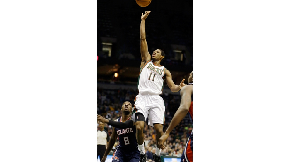 Milwaukee Bucks' Brandon Knight (11) puts up a shot against the Atlanta Hawks' Shelvin Mack (8) during the second half of an NBA basketball game Saturday, Jan. 25, 2014, in Milwaukee. (AP Photo/Jeffrey Phelps)