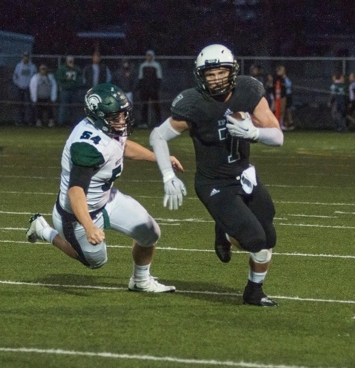 Sheldon Irish running back Jared Banks (#7) runs the ball downfield with West Salem Titans offensive lineman Jake Yates close behind.  On a rainy Monday evening, Sheldon defeated West Salem 41 to 7 at their home field. The game had been postponed from Friday due to unhealthy levels of smoke in the atmosphere from nearby forest fires. Abigail Winn, Oregon News Lab