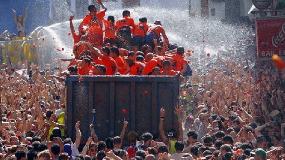 "Crowds of people throw tomatoes at each other, during the annual ""tomatina"" tomato fight fiesta, in the village of Bunol, 50 kilometers outside Valencia, Spain, Wednesday, Aug. 27, 2014. The streets of an eastern Spanish town are awash with red pulp as thousands of people pelt each other with tomatoes in the annual ""Tomatina"" battle that has become a major tourist attraction. At the annual fiesta in Bunol on Wednesday, trucks dumped 125 tons of ripe tomatoes for some 22,000 participants, many from abroad to throw during the hour-long morning festivities. (AP Photo/Alberto Saiz)"