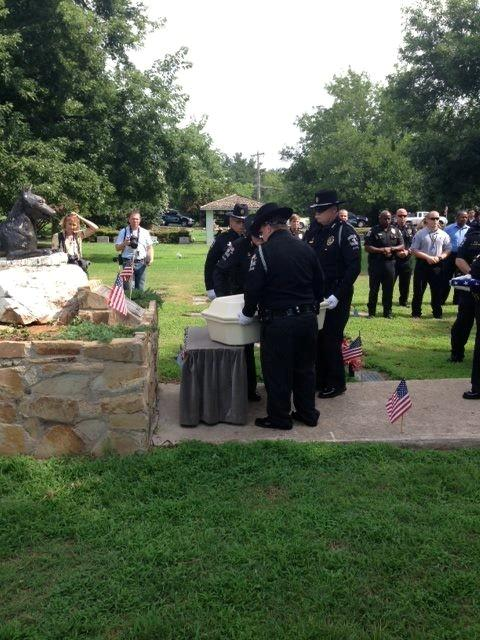 Eron's casket is loaded in front of a headstone for dogs.