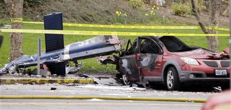 A burned out car sits adjacent to a piece of wreckage of a news helicopter Tuesday, March 18, 2014, in Seattle.