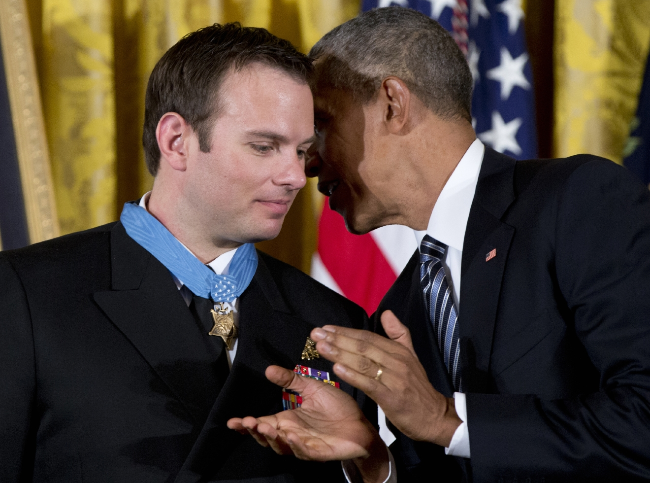 President Barack Obama applauds and leans into talk to Senior Chief Special Warfare Operator Edward Byers after presenting him with the Medal of Honor during a ceremony in the East Room of the White House in Washington, Monday, Feb. 29, 2016. U.S. Navy. Senior Chief Byers received the Medal of Honor for his courageous actions while serving as part of a team that rescued an American civilian being held hostage in Afghanistan on December 8-9, 2012. (AP Photo/Carolyn Kaster)