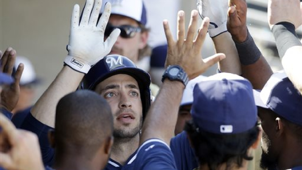 Milwaukee Brewers' Ryan Braun is congratulated by teammates after hitting a home run during the eighth inning of an exhibition baseball game against the Oakland Athletics on Wednesday, March 5, 2014, in Phoenix. (AP Photo/Morry Gash)