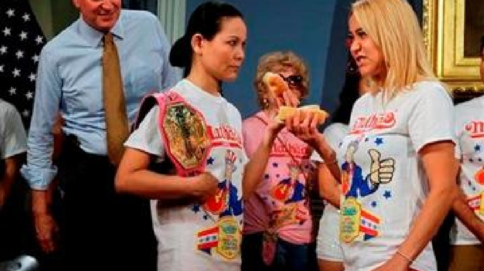 New York City Mayor Bill de Blasio watches hot dog eating contestants Sonya Thomas, left, and Miki Sudo, right, during a news conference to promote the upcoming Nathan's Famous Fourth of July Hot-Dog Eating Contest tomorrow Thursday, July 3, 2014, at City Hall in New York. Frank Franklin II/AP Photo