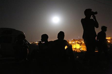 A perigee moon, also known as a supermoon, is seen behind Israelis sitting and standing on a hill at the Israeli town of Sderot, overlooking the Gaza Strip.