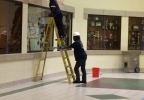 Workers clean the walls of Preble High School after extensive fire damage.