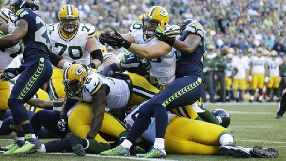 Green Bay Packers fullback John Kuhn(30) dives in for a touchdown as Seattle Seahawks outside linebacker Mike Morgan, right, tries to stop him in the first half of an NFL football game, Thursday, Sept. 4, 2014, in Seattle. (AP Photo/Elaine Thompson)