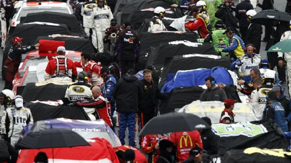 Crew members cover the cars during a weather delay at the NASCAR Sprint Cup series auto race at Bristol Motor Speedway, Sunday, March 16, 2014, in Bristol, Tenn. (AP Photo/Wade Payne)