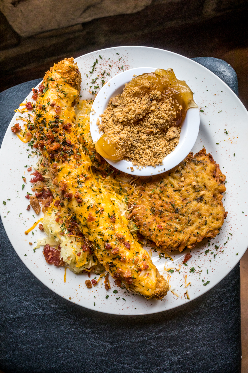Bier Cheese Mettwurst: breaded mettwurst served on a bed of sauerkraut, smothered in haus-made bier cheese, cheddar cheese, and bacon served with a potato pancake and caramelized apples / Image: Catherine Viox{ }// Published: 8.10.20
