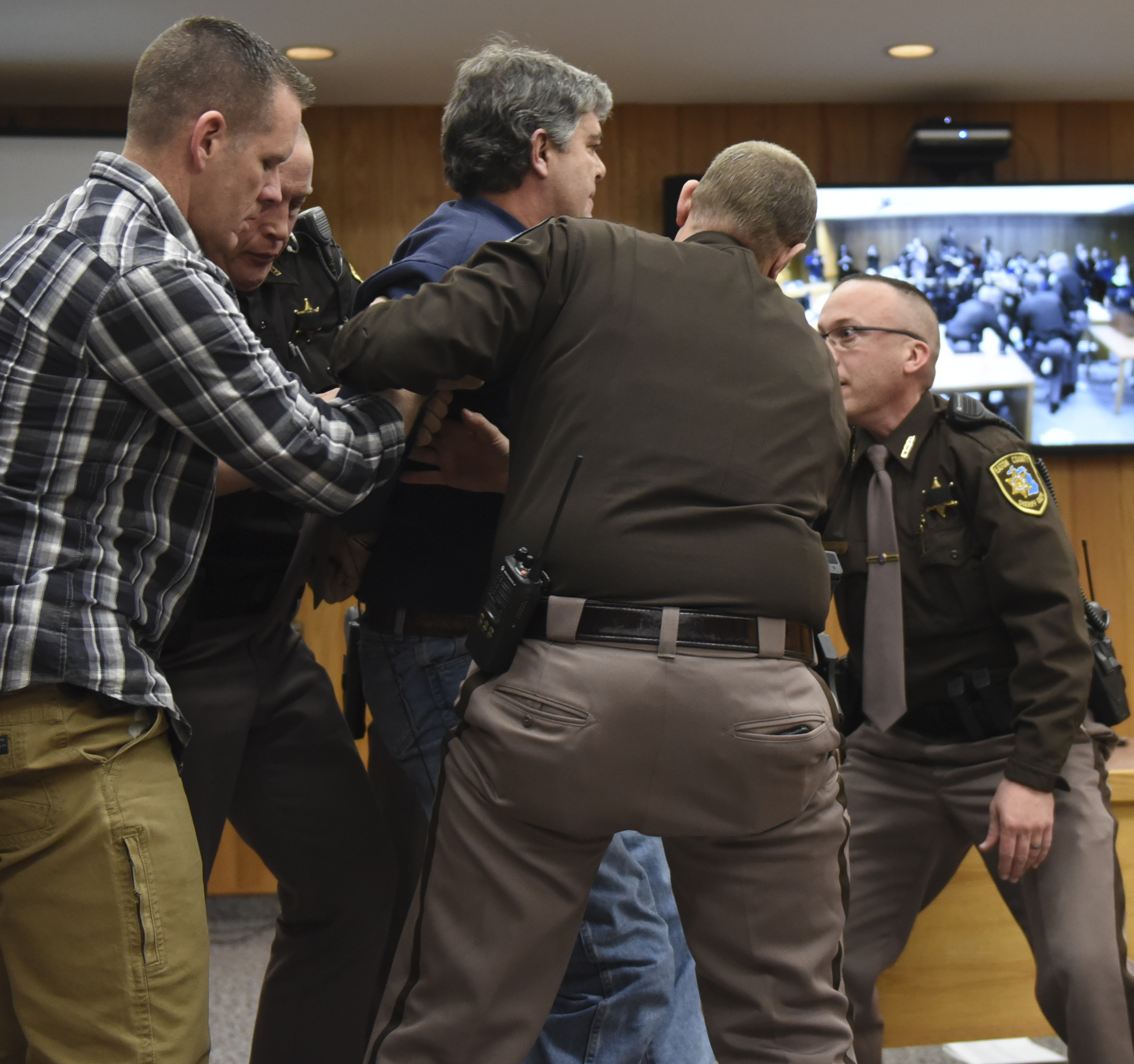 Eaton County Sheriff's deputies restrain Randall Margraves, father of three victims of Larry Nassar, Friday, Feb. 2, 2018, in Eaton County Circuit Court in Charlotte, Mich.  The incident came during the third and final sentencing hearing for Nassar on sexual abuse charges. The charges in this case focus on his work with Twistars, an elite Michigan gymnastics club.   (Matthew Dae Smith/Lansing State Journal via AP)