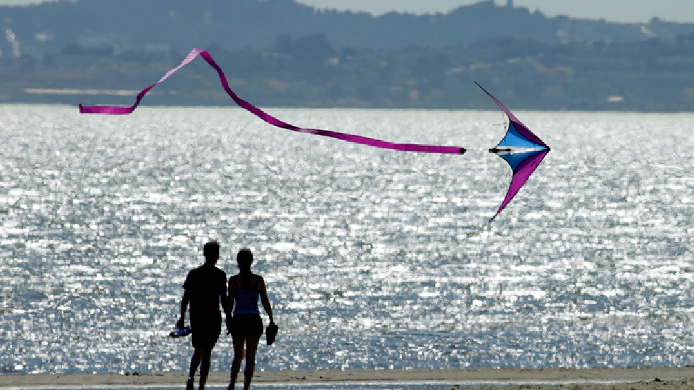 A kite flys past a couple on Crown Memorial Beach Monday, May 12, 2014, in Alameda, Calif. (AP Photo/Ben Margot)