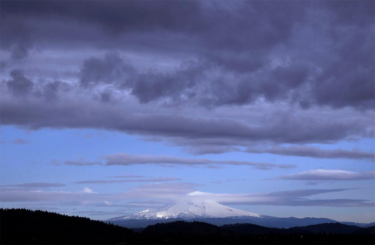 Streams of clouds skim across the peak of Oregon's Mount Hood as a darker bank of clouds heads east towards the mountain as seen from Portland, Ore., Tuesday, Nov. 22, 2016. Holiday travel in Oregon and the Pacific Northwest could be impacted by heavy rain in the valleys and potentially heavy snow in the higher elevations over the next few days. (AP Photo/Don Ryan)