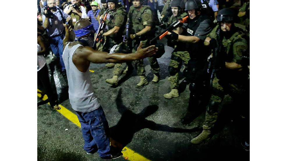 Police arrest a man as they disperse a protest in Ferguson, Mo., early Wednesday, Aug. 20, 2014. On Saturday, Aug. 9, a white police officer fatally shot unarmed 18-year-old Michael Brown, who was black, in the St. Louis suburb. (AP Photo/Charlie Riedel)