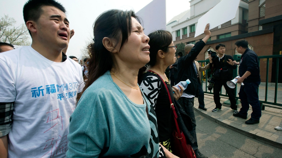 "Relatives of Chinese passengers onboard Malaysia Airlines Flight 370 cry as they protest outside the Malaysian Embassy in Beijing, China, Tuesday, March 25, 2014. Furious over Malaysia's handling of the lost jetliner a day after the country said the passengers must be dead, Chinese relatives of the missing marched Tuesday to the Malaysia Embassy, where they threw plastic water bottles, tried to rush the gate and chanted, ""Liars!"" (AP Photo/Ng Han Guan)"