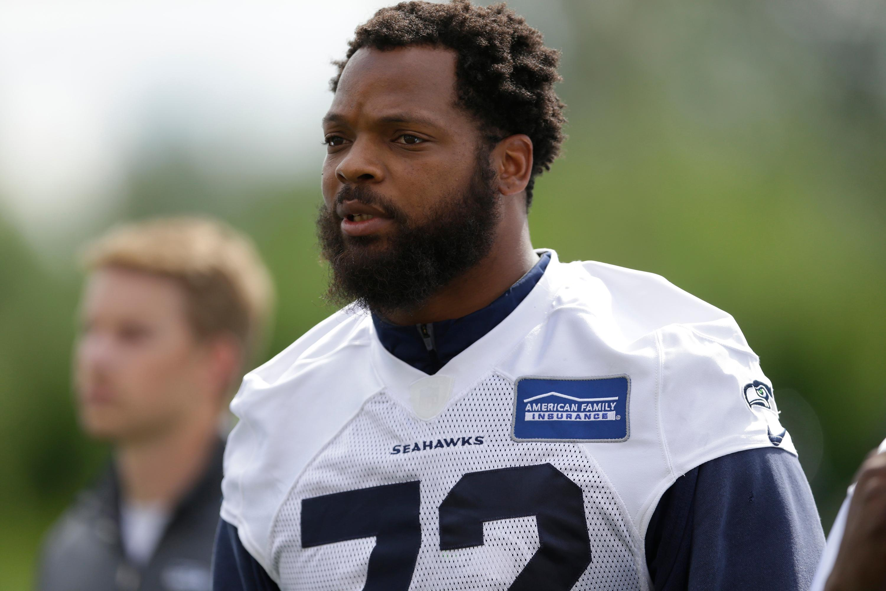 FILE - In this June 13, 2017, file photo, Seattle Seahawks defensive end Michael Bennett walks off the field following NFL football practice in Renton, Wash. Bennett said he will sit during the national anthem this season to protest social injustice and segregation. (AP Photo/Ted S. Warren, File)