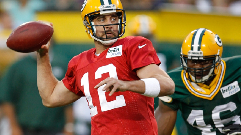 Green Bay Packers' Aaron Rodgers tries to get away from the pressure of Andy Mulumba during the Family Night scrimmage Saturday Aug. 3, 2013, in Green Bay. (AP Photo/Mike Roemer)