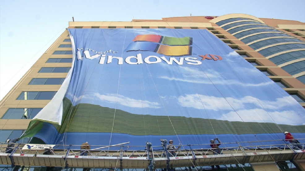 FILE - In this Nov. 8 2001 file photo, workers install a 10-story Windows XP banner on a hotel near the Las Vegas Convention Center in Las Vegas. On Tuesday, April 8, 2014, Microsoft will end support for its still popular Windows XP. With an estimated 30 percent of businesses and consumers still using the 12-year-old operating system, the move could put everything from the data of major financial institutions to the identities of everyday people in danger if they don't find a way to upgrade soon. (AP Photo/Joe Cavaretta, File)