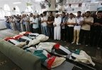 Palestinians pray at a mosque in front of the national flag-draped bodies of five members of the al-Halaq immediate and extended family, killed Sunday by an Israeli strike at their house in Gaza City, during their funeral at a mosque, Monday, July 21, 2014. On Sunday, the first major ground battle in two weeks of Israel-Hamas fighting exacted a steep price, killing scores of Palestinians and over a dozen Israeli soldiers and forcing thousands of terrified Palestinian civilians to flee their devastated Shijaiyah neighborhood, which Israel says is a major source for rocket fire against its civilians. (AP Photo/Lefteris Pitarakis)