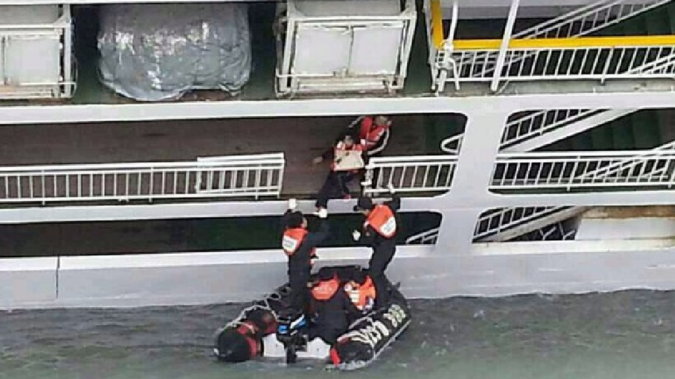 In this photo released by the South Korean Coast Guard via Yonhap News Agency, South Korean coast guard officers rescue passengers from a sinking ferry off the southern coast near Jindo, south of Seoul, South Korea, Wednesday, April 16, 2014. (AP Photo/South Korea Coast Guard via Yonhap)