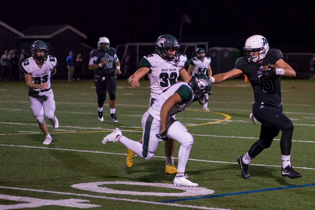 Sheldon Irish wide receiver Patrick Herbert (#5) blocks West Salem's defense. On a rainy Monday evening, Sheldon defeated West Salem at home 41 – 7. The game had been postponed until Monday, September 18, due to unhealthy levels of smoke in the air caused by nearby forest fires. Photo by Kit MacAvoy, Oregon News Lab