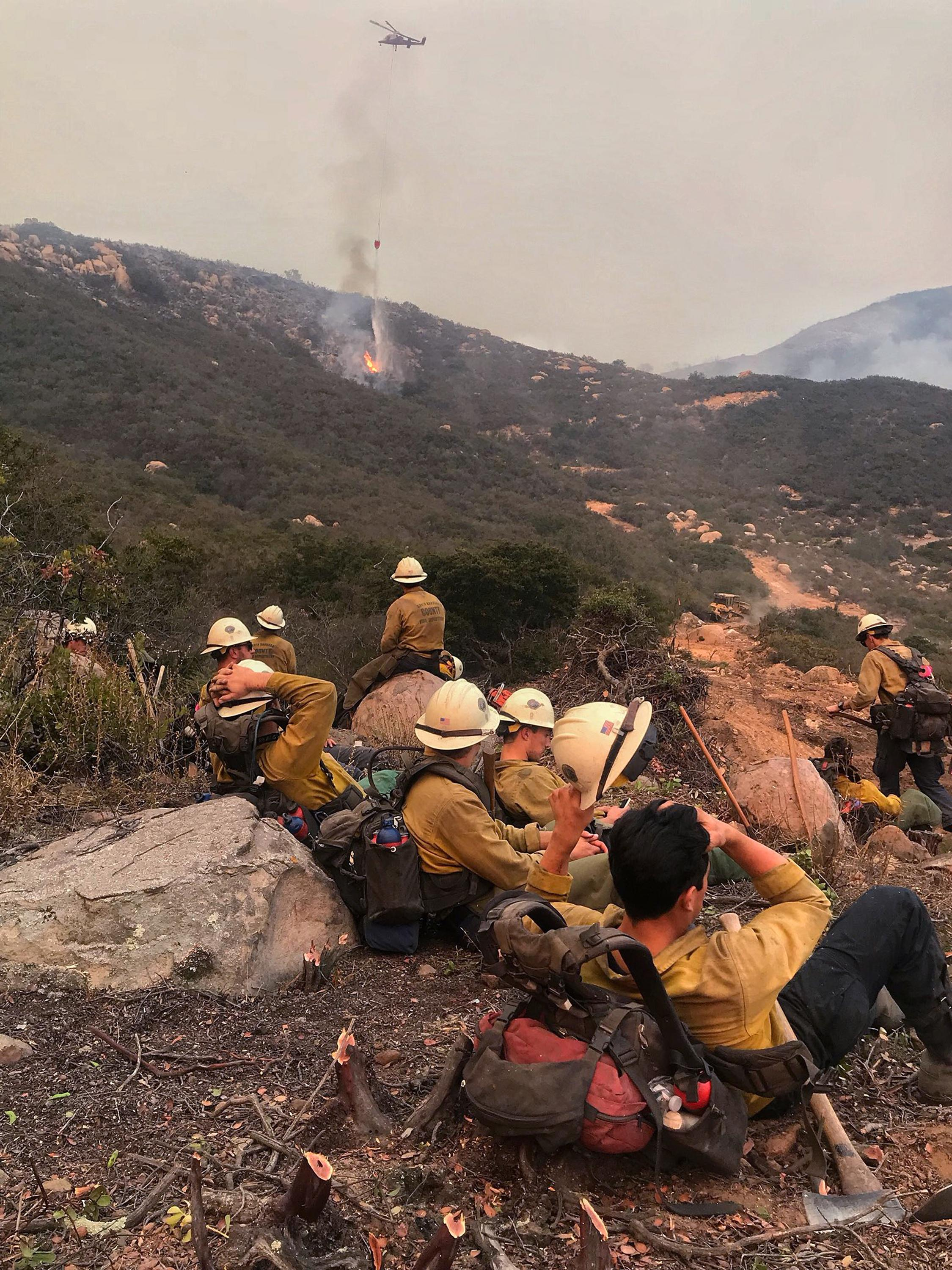 In this photo provided by the Santa Barbara County Fire Department, a Santa Barbara County Fire Crew rests after cutting a fuel break above Bella Vista Drive in Montecito, Calif., as a helicopter makes a water drop on flames as the fight against a wildfire continues Tuesday, Dec. 12, 2017. (Mike Eliason/Santa Barbara County Fire Department via AP)