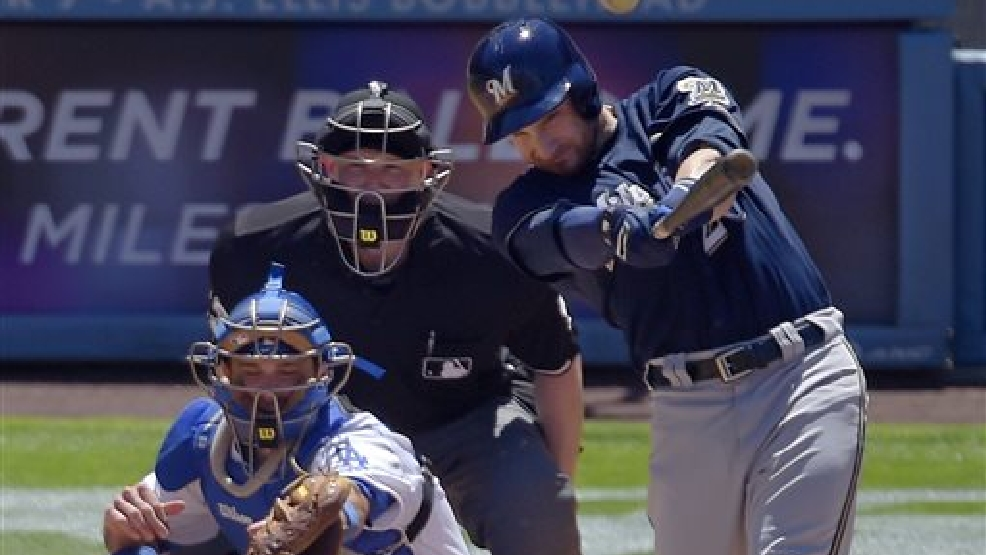 Milwaukee Brewers' Jonathan Lucroy, right, hits a three run double as Los Angeles Dodgers catcher Drew Butera, left, and home plate umpire Mike Estabrook look on during the second inning of a baseball game, Sunday, Aug. 17, 2014, in Los Angeles. (AP Photo/Mark J. Terrill)