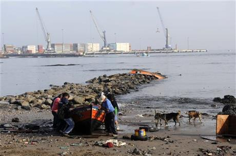 Locals inspect a boat washed ashore by a small tsunami, in the northern town of Iquique, Chile, after magnitude 8.2 earthqauke struck the northen coast of Chile, Wednesday, April 2, 2014.