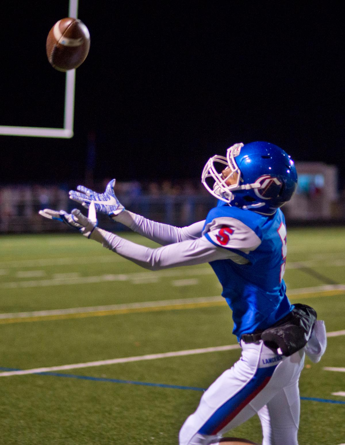 Churchill Lancers wide receiver Marshaun Tucker Jr. (#5) attempts to pull in long pass in the game against the Pendleton Buckeroos. 	The Churchill Lancers defeated the Pendleton Buckaroos 42-15, in the first round of the state 5A playoffs. Photo by Dan Morrison, Oregon News Lab